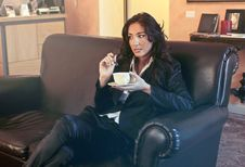Free Woman In Black Blazer Holding Teacup While Sits On Black Sofa Royalty Free Stock Photography - 109916247