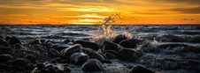 Free Waves Splashing At Stones On Beach During Sunset Stock Photo - 109916290