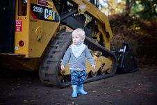 Free Baby Standing Near The CAT Skid Loader Royalty Free Stock Photo - 109916295