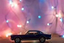 Free Selective Focus Photography Of Classic Blue Coupe Die-cast Model In Front Of String Lights On Table Stock Image - 109916321