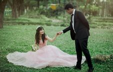 Free Man In 2-piece Suit Holding Woman In Peach-colored Wedding Gown White Holding Her Flower Bouquet Stock Image - 109916431