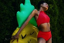 Free Woman Wearing Red Top And Bottoms Leaning On Yellow And Green Inflatable Standee Royalty Free Stock Images - 109916479