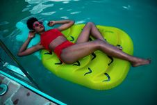 Free Woman Lying On Green Float Wearing Red Bikini Stock Photos - 109916583