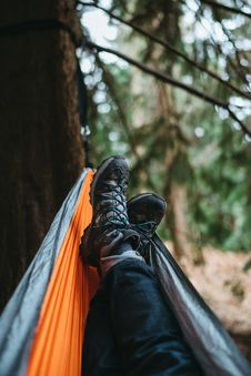 Free Person Wearing Pair Of Black Hiking Shoes Lying On Orange And Gray Hammock Stock Photos - 109916673
