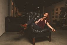 Free Woman In Maroon Scoop-neck Shirt Sitting On Black Leather Sofa Chair Royalty Free Stock Photo - 109916835