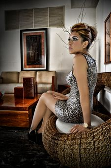 Free Woman Wearing Leopard Print Sleeveless Mini Dress Sitting On Wicker Brown Chair Royalty Free Stock Photography - 109917807