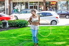 Free Woman In White Sleeveless Shirt And Blue Pants Holds Yellow Hula Hoop Stands On Green Grass Stock Photos - 109918003