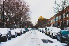Free Snow Covered Road And Inline Parked Vehicles Between 2-storey Buildings Under White Sky Royalty Free Stock Photo - 109918125