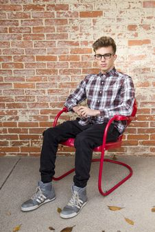 Free Man Wearing White And Red Long Sleeve Shirt Sitting On Red Steel Armchair Royalty Free Stock Photography - 109918527