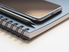 Free Closeup Photo Of Black Smartphone Near Black And Grey Pencil On Black Spiral Notebook Stock Photos - 109918743