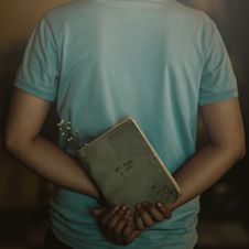 Free Man Wearing T-shirt Holding Book Stock Photography - 109918912