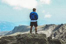Free Man Wearing Blue Hoodie Standing On Top Of Mountain Stock Images - 109919044