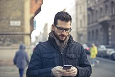 Free Man Wearing Black Zip Jacket Holding Smartphone Surrounded By Grey Concrete Buildings Royalty Free Stock Image - 109919266