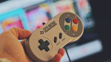 Free Person Holding White Snes Controller Royalty Free Stock Image - 109919716