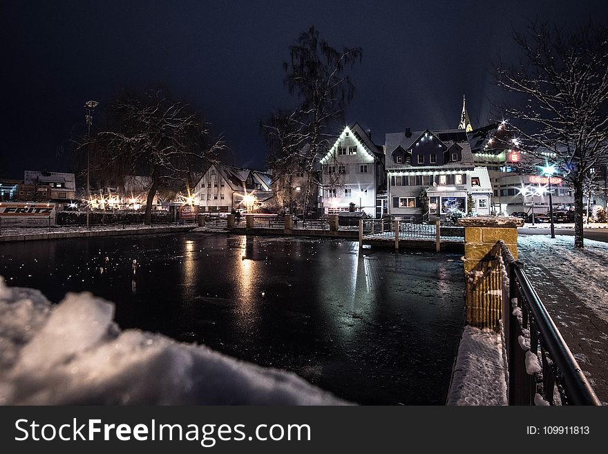 Body of Water Infront of White 3-storey Houses during Night Time