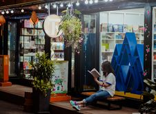 Free Woman Sitting Down On Bench And Reading Infront Of Store Stock Image - 109920181