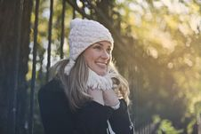 Free Photography Of Woman In Black Jacket And White Knit Cap Smiling Next To Black Metal Fence Stock Image - 109920231