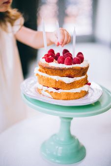 Free Girl Putting A Candle On 3-layered Cake Stock Images - 109920714