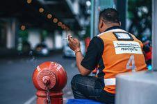 Free Man Wearing Orange And Black Polo Shirt Holding Cigarette Stock Photography - 109920822