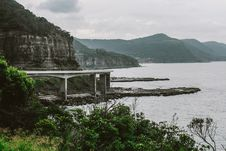 Free Concrete Bridge Near Mountain Above Shoreline Under Cloudy Sky Royalty Free Stock Photography - 109920927