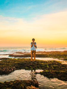 Free Man Standing On Rocks Near Beach During Golden Hour Royalty Free Stock Photo - 109921075