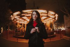 Free Woman Wearing Black Leather Jacket And Red Turtle-neck Shirt Standing In Front Of Carousel Ride Stock Photography - 109921312