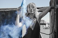 Free Woman With Halter-strap Top And Layer Necklace Holds Black Tube With Smoke Stock Images - 109922044