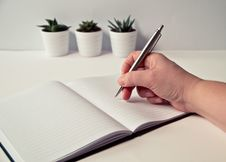 Free Person Holding Silver Retractable Pen In White Ruled Book Stock Image - 109922251