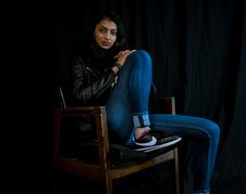 Free Woman Wearing Blue Jeans Sitting On Brown Wooden Armchair Stock Photo - 109922360