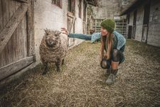 Free Woman Holding Sheep Beside Wall Stock Photography - 109922752