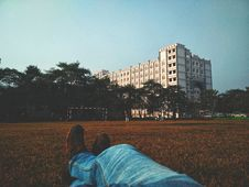Free Person In Blue Denim Jean Lying On Brown Grass Field Looking At White Multi-storey Building Royalty Free Stock Photos - 109923098
