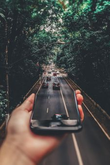 Free Forced Perspective Photography Of Cars Running On Road Below Smartphone Royalty Free Stock Images - 109923159