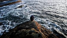 Free Photography Of Person Sitting On Rock Near Ocean Royalty Free Stock Photography - 109923297