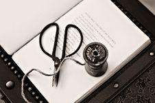 Free Black Scissors Near Thread Reel On White Book Page Stock Photos - 109923443