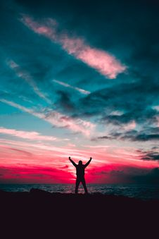 Free Silhouette Of Man Raising Hands Against A Red Sunset Light Under Green Clouds Royalty Free Stock Photo - 109923495