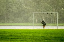 Free Person In Black Hoodie Riding Swing While Raining Stock Image - 109923811