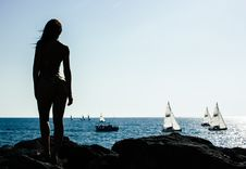 Free Woman Standing On Rock With Sailing Boats On Sea Stock Photography - 109924062