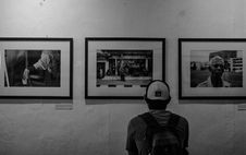 Free Grayscale Photo Of Man Wearing White Cap In Front Of Three Paintings Royalty Free Stock Images - 109924069