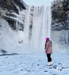 Free Woman Wearing Pink Snow Coat Standing On Field Full Of Snow In Front Of Frozen Waterfalls Stock Images - 109924444