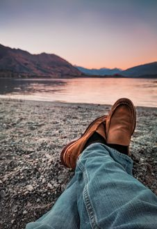 Free Person Wearing Blue Jeans And Brown Leather Loafers Sitting Beside Gray Sand Stock Photography - 109924452