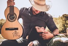 Free Woman In Green Top With Man In Black Long-sleeved Shirt Holding Autographed Brown Guitar Royalty Free Stock Photos - 109924568
