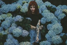 Free Woman With Black And Red Flower Tattoo Standing Behind Blue Flowers Royalty Free Stock Photography - 109924787