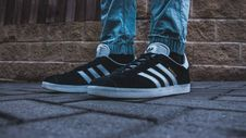 Free Person Wearing Pair Of Black-and-white Adidas Gazelle Royalty Free Stock Images - 109924989