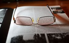 Free Eyeglasses With Gold-colored Frame On Opened Book Stock Images - 109925214