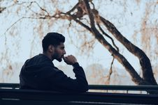 Free Man In Black Hoodie Sitting On Bench Near Green Trees Royalty Free Stock Images - 109925429