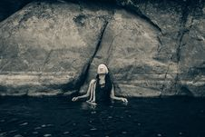 Free Woman In Blindfold Wearing Black Top On Body Of Water While Leaning On A Rock Stock Photo - 109925740