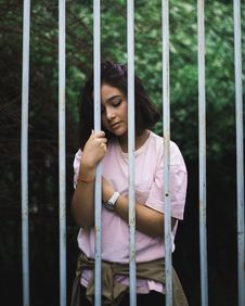 Free Woman Wearing Pink Crew-neck T-shirt Standing And Leaning Behind White Bars Royalty Free Stock Photos - 109925748