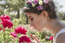 Free Woman In Floral Headdress Sniffing On Red Flowers Royalty Free Stock Photography - 109925857