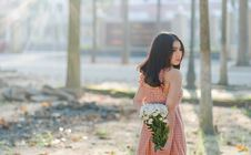 Free Woman Wearing Orange Sleeveless Dress Holding A Bouquet Of Flowers Stock Photography - 109926132