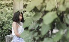 Free Woman Wearing White Spaghetti Strap Top Sitting In Garden Stock Images - 109926674